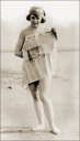 Royalty Free Photo of a Woman Standing on a Beach Wrapped in a Newspaper