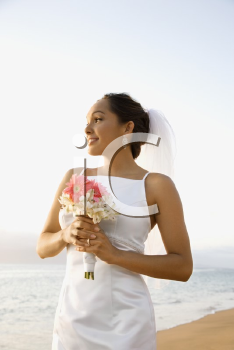 Royalty Free Photo of a Bride Holding a Bouquet on the Beach