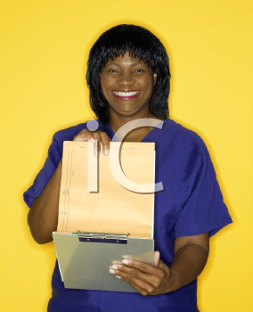 Royalty Free Photo of a Woman in a Medical Uniform Smiling Reading a Chart