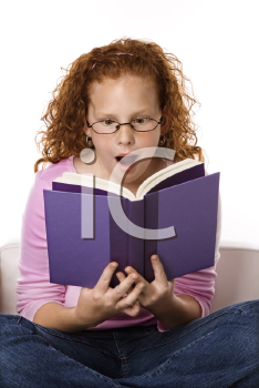 Royalty Free Photo of a Little Girl Sitting and Reading Book Looking Surprised