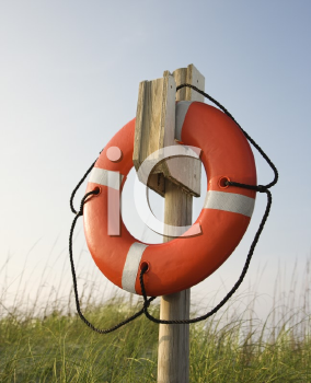 Royalty Free Photo of a Life Preserver Hanging on a Post on a Beach in Bald Head Island, North Carolina