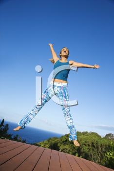 Caucasian mid-adult woman jumping into air with arms and legs outstretched.