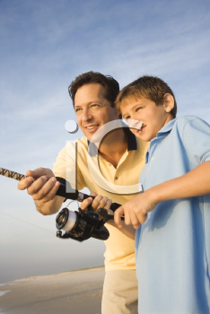 Royalty Free Photo of a Man Shore Fishing on a Beach With a Preteen Boy
