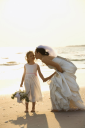 Royalty Free Photo of a Bride Kneeling to Give the Flower Girl a Kiss on the Cheek