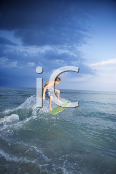 Royalty Free Photo of a Teen Riding a Skimboard
