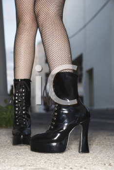 Royalty Free Photo of Legs and Feet Wearing High Heeled Boots in an Urban Setting