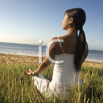Royalty Free Photo of a Woman Meditating on a Beach