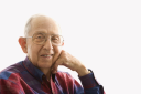 Royalty Free Photo of a Smiling Elderly Man With His Face Propped on His Hand