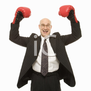 Royalty Free Photo of a Smiling Businessman Standing With Arms Raised Wearing Boxing Gloves