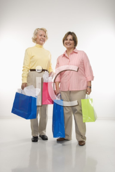 Royalty Free Photo of a Senior Woman and Middle-aged Woman Holding Gift Bags and Smiling