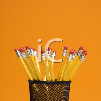Group of pencils in pencil holder on orange background.