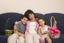 Royalty Free Photo of a Mother With Her Son and Daughter at Home Sitting With Easter Baskets