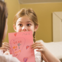 Royalty Free Photo of a Girl Giving Her Mother a Drawing