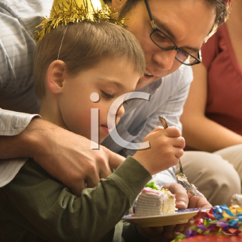 Caucasian mid adult father helping son with birthday cake.