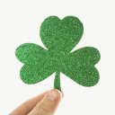 Royalty Free Photo of a Hand Holding a Green Glitter Paper Shamrock