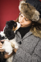 Royalty Free Photo of a Young Woman Wearing a Fur Hat Kissing a King Charles Spaniel