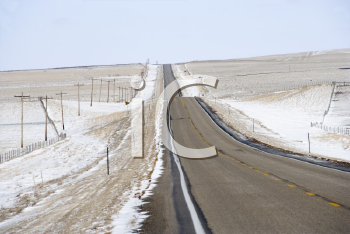 Royalty Free Photo of a Road Over a Rolling Hill Landscape With Snow and Power Lines