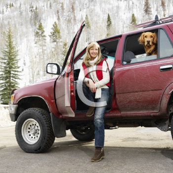 Royalty Free Photo of a Woman Sitting in a Dirty SUV with a Dog in the Back Seat