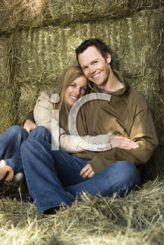 Royalty Free Photo of a Couple Sitting on Hay Hugging and Smiling