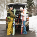 Royalty Free Photo of a Couple Unloading Ski Equipment From a Vehicle Smiling and Laughing