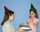 Royalty Free Photo of a Girl Wearing a Party Hat With Mother Holding a Birthday Cake