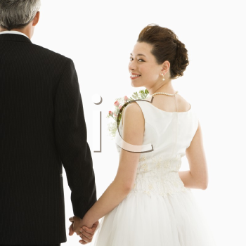 Royalty Free Photo of a Bride Looking Over Her Shoulder While Holding Her Groom's Hands