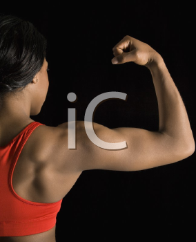Back view of African American woman flexing muscular bicep.
