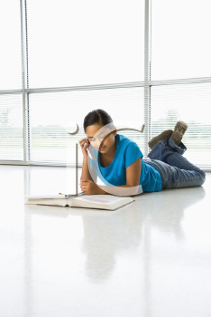 Royalty Free Photo of a Preteen Girl Lying on the Floor Doing Homework While Talking on a Cellphone