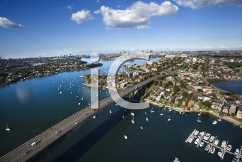 Royalty Free Photo of an Aerial View of Victoria Road Bridge and Boats With Distant Downtown Skyline in Sydney, Australia