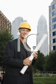 Royalty Free Photo of a Businessman Wearing a Hard Hat Holding Blueprints