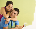 Royalty Free Photo of a Happy Smiling Couple Painting the Interior Wall at Home