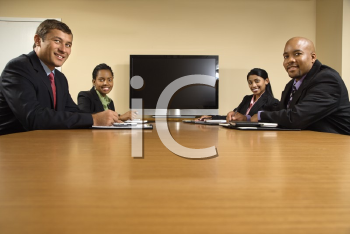 Royalty Free Photo of Businesspeople Sitting at a Conference Table Smiling