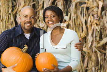Royalty Free Photo of a Couple Sitting on Hay Bales and Holding Pumpkins at an Outdoor Market
