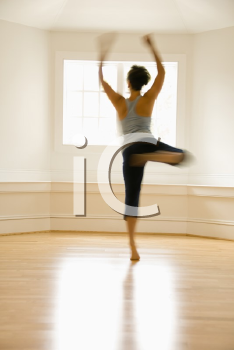 Royalty Free Photo of a Young Woman in Dancing By a Sunlit Window