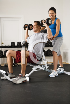 Royalty Free Photo of a Woman Assisting a Man Lifting Weights at a Gym