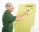 Royalty Free Photo of a Man Painting a Wall Green With a Paint Roller