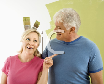 Royalty Free Photo of a Couple Standing in Front of a Wall While a Man Makes Bunny Ears With Paintbrushes
