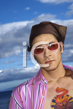 Portrait of a young man with sunglasses and headscarf at the beach. Vertical shot.