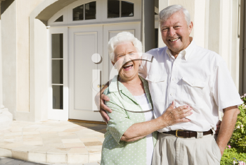 Royalty Free Photo of a Senior Couple Outside Their Home