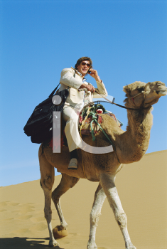 Royalty Free Photo of a Man on a Camel in the Desert With a Cellphone