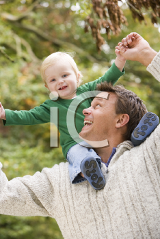 Royalty Free Photo of a Father Giving a Piggyback Ride