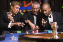 Royalty Free Photo of Three Men Around a Roulette Table