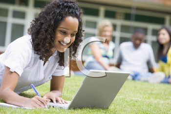 Royalty Free Photo of a Student Working on a Laptop With Others Behind Her