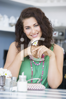 Royalty Free Photo of a Woman at a Table Holding a Daisy