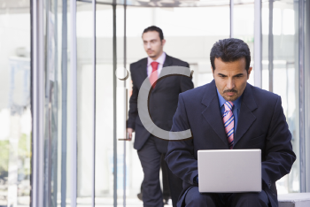 Royalty Free Photo of a Man With a Laptop and Another Man Behind Him