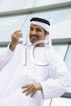 Royalty Free Photo of a Middle Eastern Man Outside an Office Building With a Headset