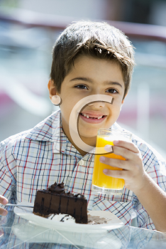 Royalty Free Photo of a Boy Eating Dessert and Drinking Juice