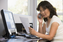 Royalty Free Photo of a Woman Looking at Papers Talking on the Telephone