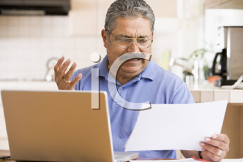 Royalty Free Photo of a Man Looking Frustrated While Holding a Paper