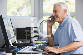 Royalty Free Photo of a Man at a Computer Talking on a Telephone